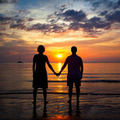Silhouettes young couple on the beach at sunset, romantic picture — Zdjęcie stockowe