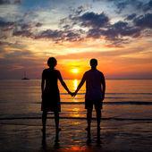 Silhuetter unga par på stranden vid solnedgången, romantisk bild — Stockfoto