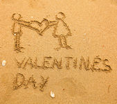 Texture on the sand: Happy Valentine's Day and a pair holding a big heart — Stock Photo