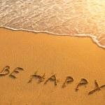 The inscription on the beach sand: Be Happy — Stock Photo #19724673