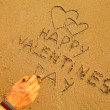 Female hand writes in the beach sand: Happy Valentine's Day and draws two hearts — Stock Photo #19724739
