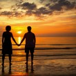 Royalty-Free Stock Photo: Romantic picture: Silhouettes young couple on the beach at sunset.