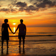 Romantic picture: Silhouettes young couple on the beach at sunset. — Stock Photo