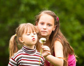 Cute 5 year old and 11 year old (looks into the camera) girls blowing dandelion seeds away. — Stockfoto