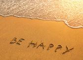 надпись на песчаном пляже: be happy — Стоковое фото