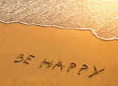 The inscription on the beach sand: Be Happy — Photo