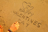 Female hand writes in the beach sand: Happy Valentine's Day and draws two hearts — Stock Photo