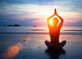 剪影年轻女子在日落时练瑜伽在海滩上. — 图库照片