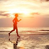 Jeune femme jogging sur la plage au coucher du soleil — Photo