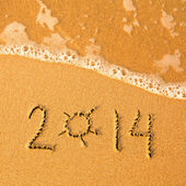 2014 written in sand on beach texture - soft wave of the sea. — Foto Stock