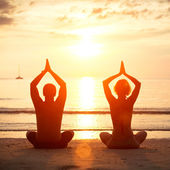 Yoga practice, young couple sitting on the beach of the sea in the lotus position at sunset. — Stock Photo