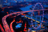 Aerial view on Singapore Flyer from roof Marina Bay Sands at night. — Stock Photo