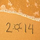 2014 escrito en la arena en la textura de la playa - la onda suave del mar. — Foto de Stock