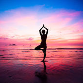 Young woman yoga practice at the seaside at sunset — Stock Photo