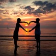 Young couple holding hands heart-shaped on the sea beach at sunset. — Stock fotografie