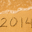 2014 written in sand on beach texture. Soft wave of the sea. — Stock Photo