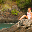 Blonde girl is sitting on the rocks at the seaside — Stock Photo