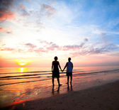 Young couple holding hands on the sea beach at sunset. — Stock Photo
