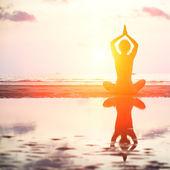 Femme d'yoga assis en posture de lotus sur la plage pendant le coucher du soleil. — Photo