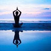 Yoga, harmoni för hälsa - siluett ung kvinna på stranden vid solnedgången. — Stockfoto