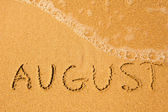 August - written in sand on beach texture - soft wave of the sea. — Stock Photo