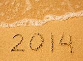 2014 scritto nella sabbia sulla trama di spiaggia. morbida onda del mare. — Foto Stock