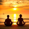 A young couple sitting on the beach of the sea in the lotus position at sunset, yoga practice. — Stock Photo