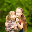 Cute 5 year old and 11 year old girls blowing dandelion seeds away. — Stock Photo