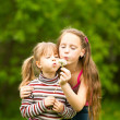 Cute 5 year old and 11 year old girls blowing dandelion seeds away. - Stock Photo
