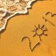 2013 written in sand on beach texture - soft wave of the sea. — Stock Photo