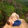 Picture of loneliness - young girl lying on top of the rock in the canyon. — Stock Photo