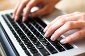 Hands typing text on a laptop keyboard — ストック写真