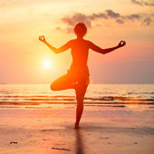 Silhouette of a beautiful yoga woman on the beach at sunset. — Stock Photo