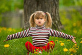 Lovely five-year girl sitting in grass and throws up his hands with regret — Stock Photo