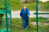 Active old woman nordic walking outdoors, 85 years old. — Stock Photo