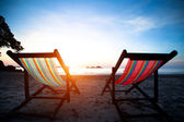 Beach loungers on the deserted coast sea at sunrise. — Stock Photo