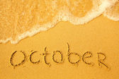 October - written in sand on beach texture — Stock Photo