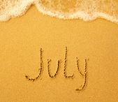 July - written in sand on beach texture — Stock Photo
