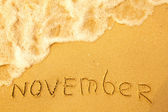 November - written in sand on beach texture — Stock Photo
