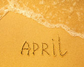 April - written in sand on beach texture — Stock Photo