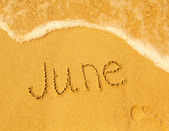 June - written in sand on beach texture — Stock Photo