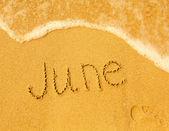 June - written in sand on beach texture — Stock Photo