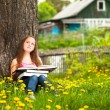 A girl, 11 years old, reads a book in the meadow — Stock Photo #20439869