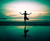 Silhouette of a beautiful yoga woman at sunset (in surreal colors) — Stock Photo