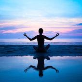 Silhouette d'un yoga de la femme sur le coucher du soleil, reflet dans l'eau mer — Photo