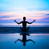 Silhouette of a woman yoga on sea sunset with reflection in water — Stock Photo