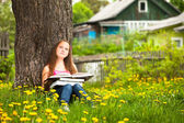 A girl, 11 years old, reads a book in the meadow — Stock Photo