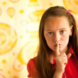 Hushing. Young girl with her finger over her mouth. — Stock Photo