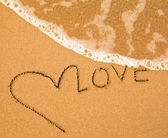 Love - text written by hand in sand on a beach, with a blue wave. — Stockfoto