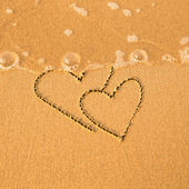 Shape of the two hearts of the sea on the beach in Valentine Day. Soft wave of the sea. — Stock Photo